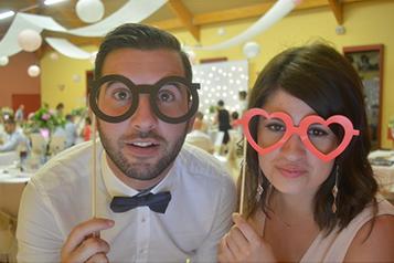 Photo prise par une borne photo de deux personnes avec de fausse lunettes dans un mariage