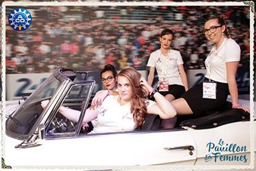 Photo prise par un photobooth de quatre femmes dans une ancienne voiture devant un fond du circuit des 24 heures du Mans