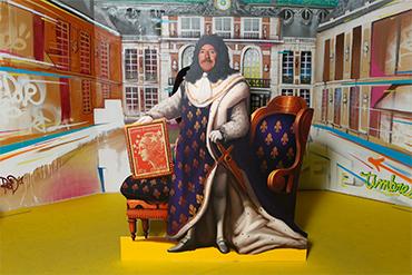Photo prise par un photobooth d'un homme à moustache passant son visage à travers un passe tête décoré à l'effigie de La Poste et des timbres