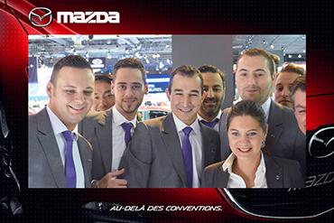 Photo prise par une borne photo d'un groupe de personne habillé en costume dans un salon automobile