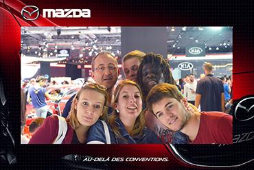 Photo prise par un photobooth d'un groupe de personnes visitant un salon automobile