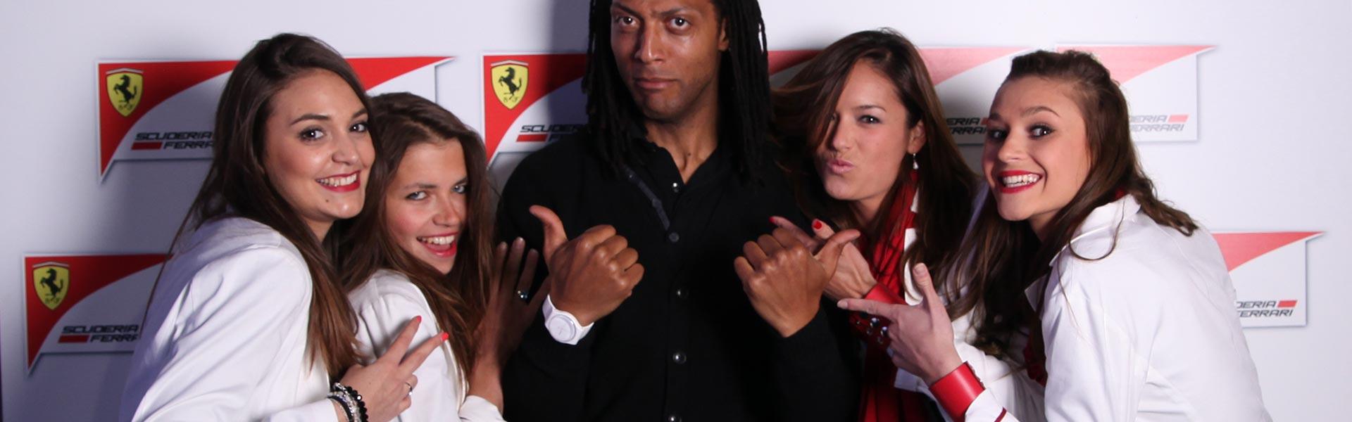 Un homme et les quatre femmes positionnées à côtés de lui se font photographier par un photobooth devant un fond à l'effigie de la marque Ferrari