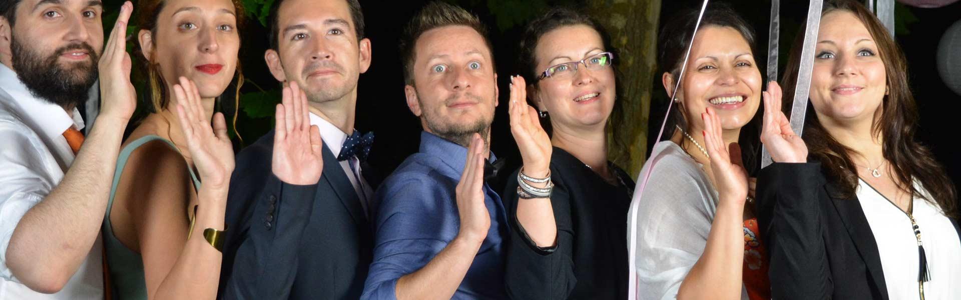 Photo prise par une borne photo d'un groupe de personne faisant un signe de la main